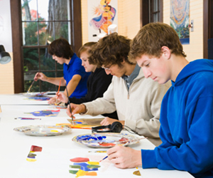 This is a photo of high school students painting in an art classroom.