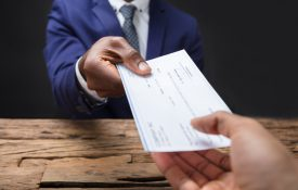 Businessperson hand passing over a check to another hand across a table