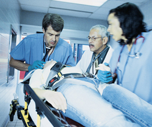 This is a photo of doctors and nurses attending to a patient on a gurney in a hospital.