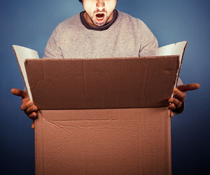 This is a photo of a surprised man looking into a box.
