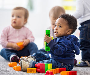 This is a photo of three infants playing with blocks.