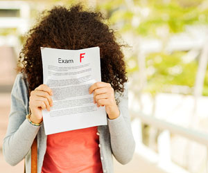 This is a photo of a girl holding an exam with a failing grade.