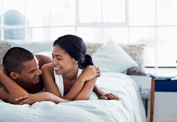 Happy-looking couple lying in bed