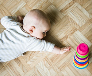 This is a photo of an infant reaching toward a toy.