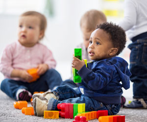 This is a photo of infants playing with blocks.