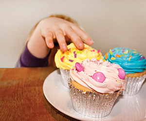 This is a photo of a child sneakily grabbing a cupcake.