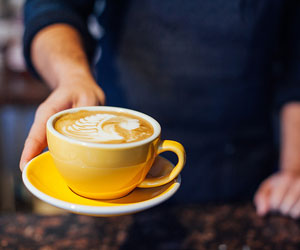 This is a photo of a person handing over a latte in a mug.