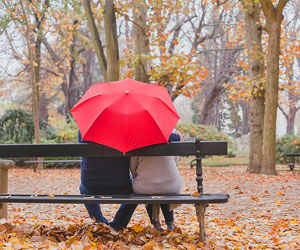 This is a picture of a couple sitting on a bench, sharing an umbrella.