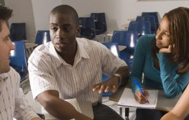 Students talking in a classroom, featured image for student benefits page.