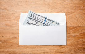 Top view of blank envelope with dollar banknotes on wooden desktop.