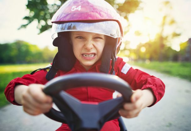 Little boy aged 6 driving a pedal go-kart, kart, soapbox car or cyclekart. Little boy is angry and clenching his teeth. He is obviously very focused on winning the race. Road and sunset visible in the background.