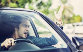 Well-dressed male driver angrily yelling at traffic.