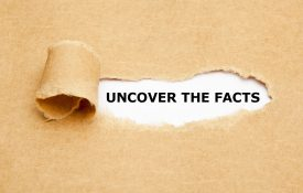 "This is a photo of a piece of paper torn to reveal the phrase ""uncover the facts"""