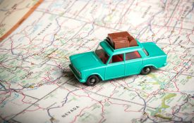 Vintage toy car with luggage on the roof with a road map of the U.S.