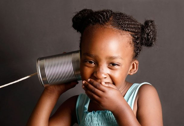 "This is a photo of a girl ""listening"" to a tin can phone."