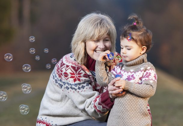 Grandmother and granddaughter blowing bubbles