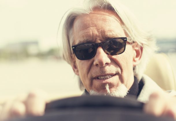 outdoor portrait of a modern senior man with long hair and beard driving a convertible classic car.