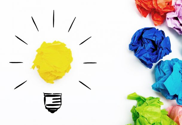 Crumpled paper light bulb over white background, surrounded by crumpled colorful paper.