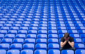 Man with head in his hands in empty stadium