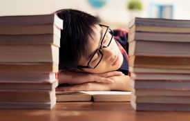 Student sleeping between piles of books