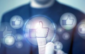 Social Media Likes and Social Marketing Concept with Businessman Touching Glowing Like Icon.