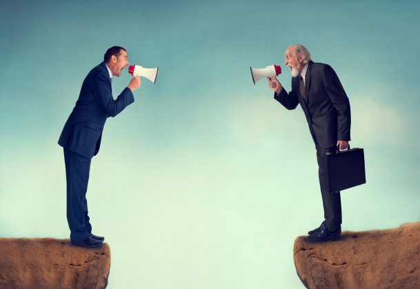 Two Businessmen in Suits Shouting at Each Other Through a Loudspeaker
