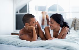 Shot of a happy young couple talking together while lying in bed
