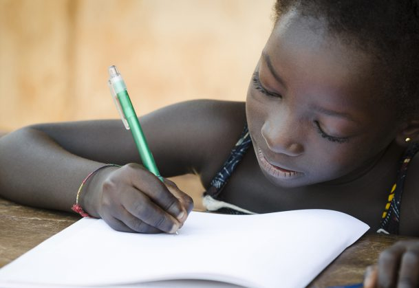 A young African girl writing her lesson on a sheet of paper.