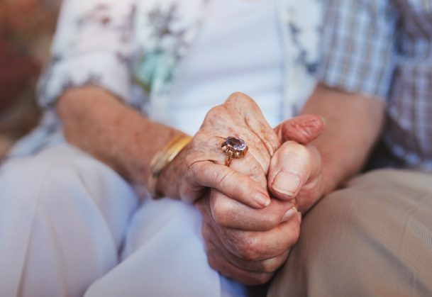Cropped shot of elderly couple holding hands while sitting together at home.