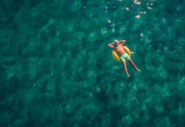 This is a high-angle-view photo of a senior man relaxing while floating in the ocean using swimming tube