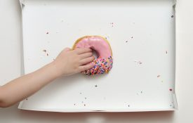 Overhead view of a doughnut box with a young girl's hand reaching to grab the last pink strawberry frosted donut.