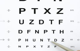 Ballpoint pen pointing to letter on eye exam chart.
