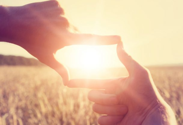 This is a photo of a woman using her hands to frame distant sun rays