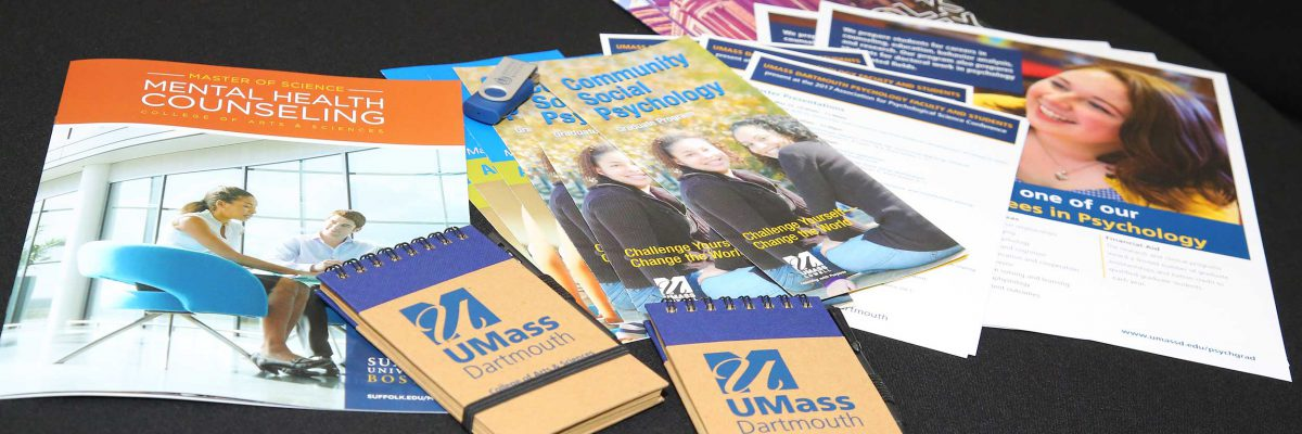 A collection of APS promotional materials spread out on a table.
