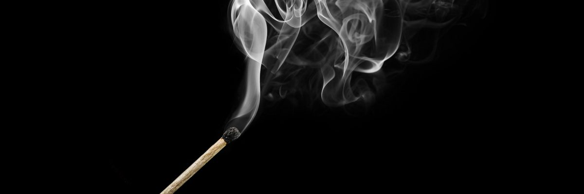 Burnt match with curls of smoke isolated on black