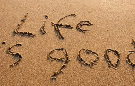 This is a photo of the words 'life is good' written on a beach