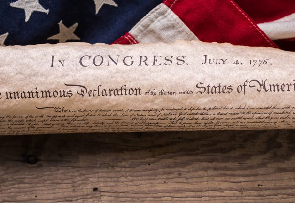 United States Declaration of Independence rolled in a scroll on a vintage American flag and rustic wooden board