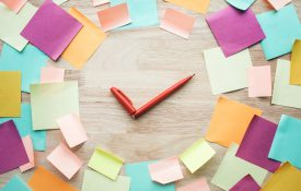 Sticky notes in a clock-like circle with pens as the clock hands