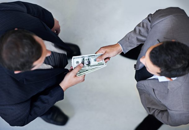 This is a photo of two men exchanging cash