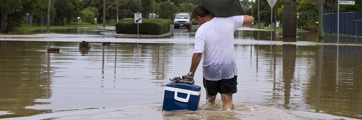 A man leaving his home walking through flood waters.