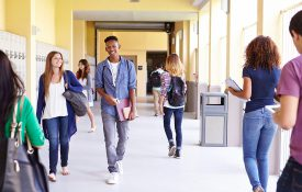 Group Of High School Students Walking Along Hallway