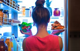 A young woman standing in front of the refrigerator, holding a bowl of salad in one hand and a plate of fried chicken in the other.