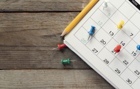 Closeup shot of calendar with push pins on certain dates