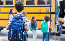 Child waiting as classmates board schoolbus