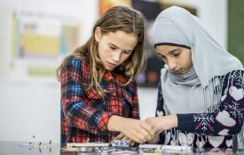 Two girls working together with wires and circuits during science class.