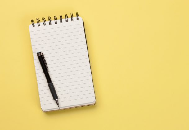 Blank lined notepad with a pen on a yellow surface