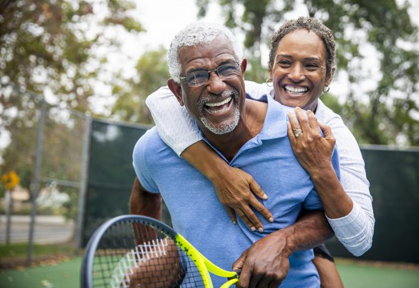 A senior couple together on the tennis court.