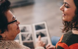 This is a photo of an older woman and a younger woman looking at a photo album
